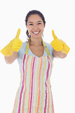 Happy woman giving thumbs up in rubber gloves