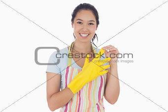 Smiling woman taking off rubber gloves
