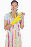 Woman in apron taking off rubber gloves