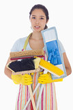Frowning woman holding brushes and mops