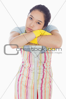 Frowning woman leaning on mop