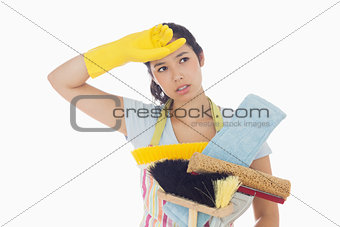 Weary woman holding cleaning tools