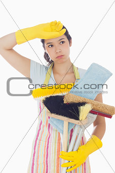 Overworked woman holding cleaning tools