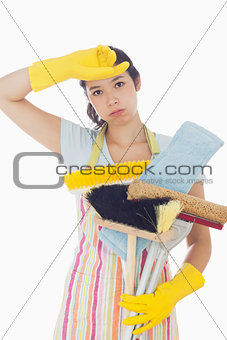 Tired woman holding cleaning tools
