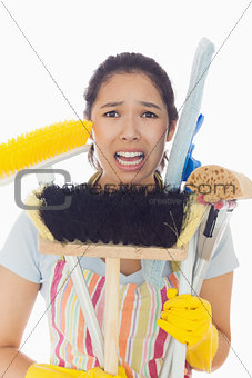 Distressed woman holding cleaning tools