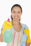 Smiling woman holding spray bottle and cloth