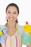 Happy woman holding spray bottle and rag