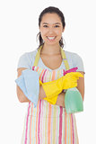 Woman standing with arms crossed holding cleaning products
