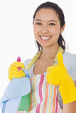 Smiling woman with cleaning products giving thumbs up