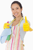 Woman holding cleaning products giving thumbs up