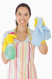 Smiling woman holding up rag and spray bottle