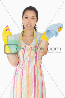 Overworked woman holding rag and spray bottle