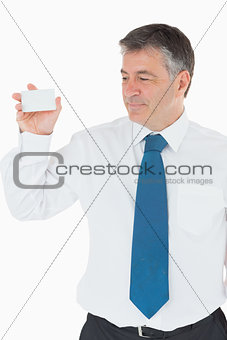 Smiling businessman showing card