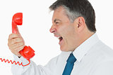 Businessman screaming in phone receiver