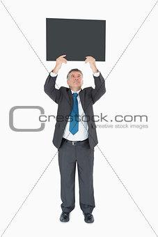 Smiling businessman holding blackboard