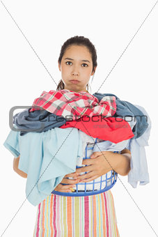 Tired woman holding full laundry basket