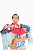 Overworked woman holding basket full of laundry