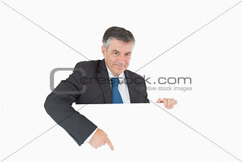 Smiling businessman pointing to board