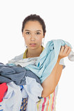 Tired woman holding dirty laundry