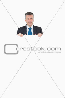 Smiling businessman looking over top of board