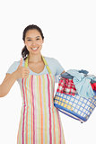 Laughing woman holding laundry basket full of dirty clothes