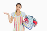 Puzzled young woman holding laundry basket full of dirty laundry