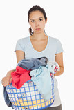 Bored woman holding a basket overflowing of laundry