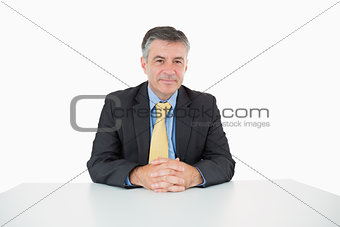 Well-dressed man sitting at his desk