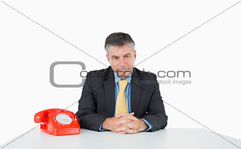 Calm man sitting at his desk with a phone
