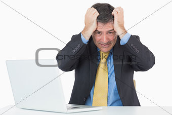 Troubled man sitting at his desk with a laptop