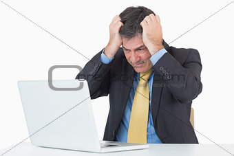 Anxious man sitting at his desk with a laptop