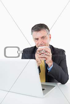Smiling man drinking coffee at his desk