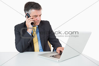 Man phoning while writing on laptop