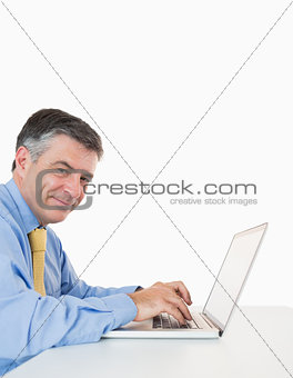 Happy man typing on a laptop