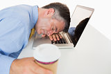 Exhausted man sleeping on his laptop while holding coffee