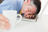 Man sleeping on his laptop while holding coffee