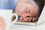 Businessman sleeping on his laptop while holding coffee