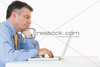 Tired man writing on his laptop