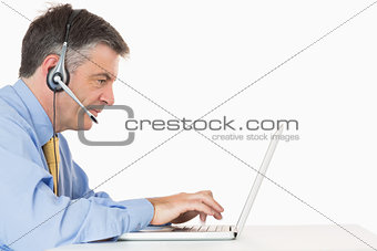 Serious man with headset typing on laptop