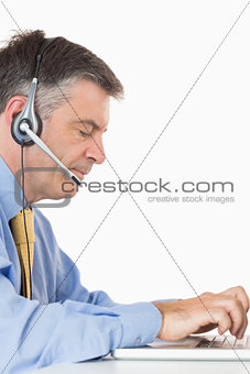 Businessman with headset writing on laptop