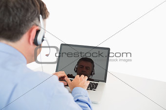 Businessman with headset working on laptop