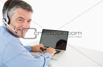 Smiling businessman with headset working on laptop