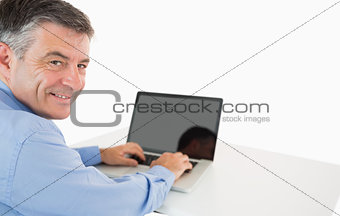 Smiling man working with laptop