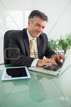 Smiling business man working on laptop