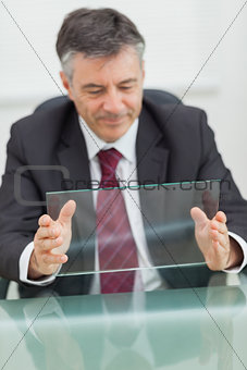 Smiling business man holding a virtual screen