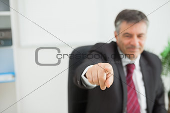 Smiling businessman pointing