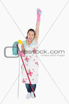 Woman holding a sponge in the air and shouting