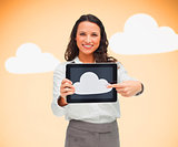Woman standing while holding a tablet pc pointing to cloud symbol on screen