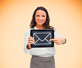 Businesswoman holding a tablet pc smiling and pointing at mail symbol