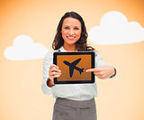 Woman pointing to airplane symbol on tablet pc
